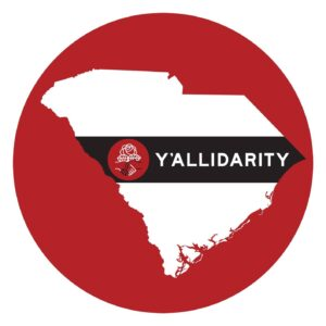 """an outline of the state of South Carolina on a deep red background.  a banner across the outline of the state reads """"Y'allidarity"""""""